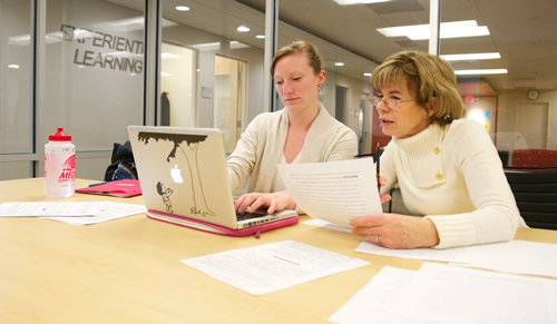 An APEX advisor holding papers and guiding a student through work on a laptop within the APEX Conference Room.