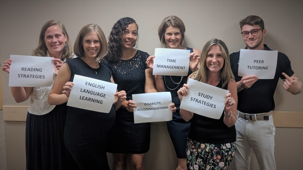 The Academic Resource Center staff, posing in a group photo. Each staff member is holding a paper sign that describes one of their focuses and services.