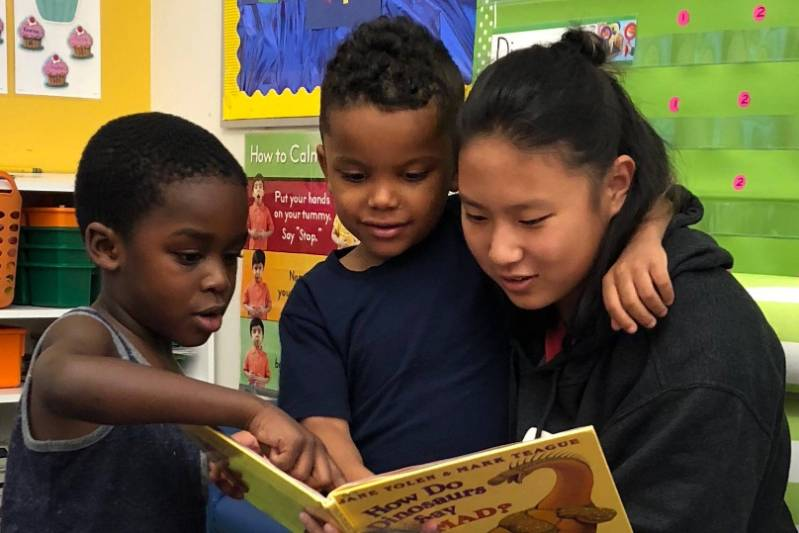 College student reading to two grade school children